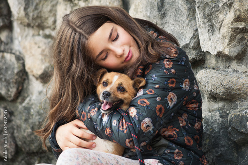 beautiful teen girl hugging her new pet adopted friend  dog from rescue shelter Wallpaper Mural