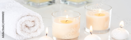 Stampa su Tela burning white candles in glass and rolled towel on marble white surface, panoram