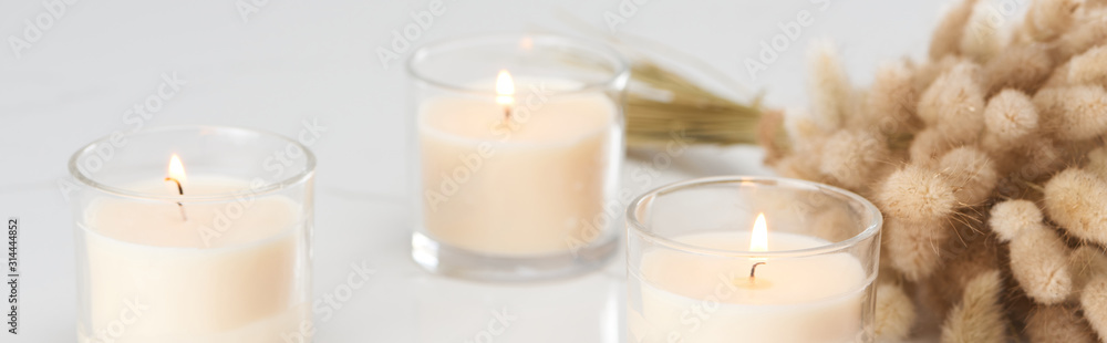 Fototapeta selective focus of fluffy bunny tail grass and burning white candles in glass glowing on marble white surface, panoramic shot