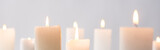 selective focus of burning white candles glowing isolated on grey, panoramic shot