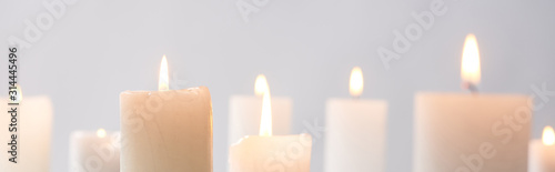 Obraz selective focus of burning white candles glowing isolated on grey, panoramic shot - fototapety do salonu