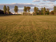 Football soccer field with goalpost in the background, freshly cut grass surface, nobody, cloudy sky, Factory roof in the background.