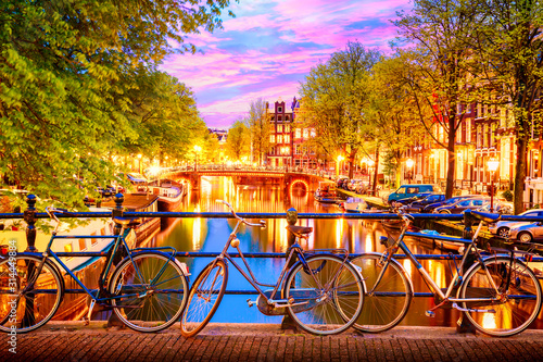 Fototapeta Amsterdam  old-bicycles-on-the-bridge-in-amsterdam-netherlands-against-a-canal-during-summer-twilight-sunset-amsterdam-postcard-iconic-view