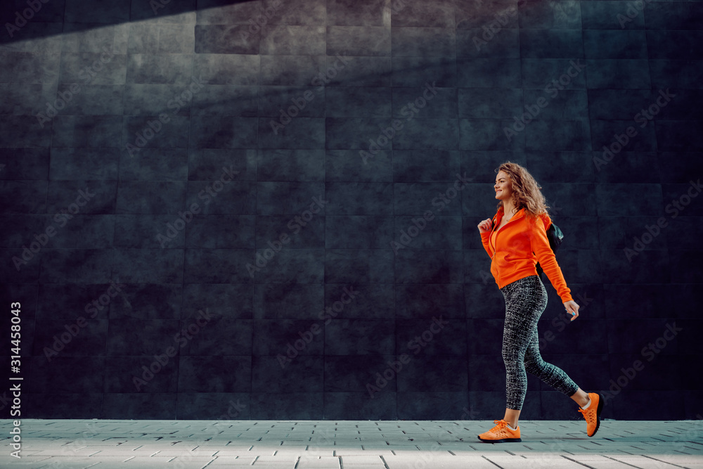 Fototapeta Full length of slim beautiful Caucasian woman in sportswear carrying bag while passing by gray wall. Gym time.