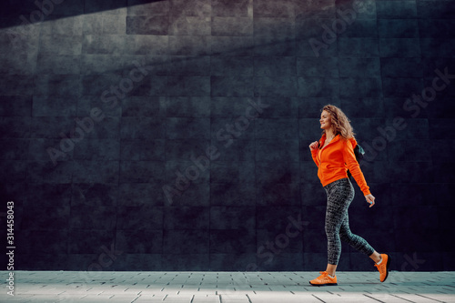 Obraz Full length of slim beautiful Caucasian woman in sportswear carrying bag while passing by gray wall. Gym time. - fototapety do salonu