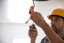 Worker Repairing Lamp On Stretch Ceiling Indoors. Space For Text