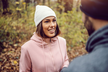 Pretty smiling young woman in sportswear, with beanie on head standing in nature,taking a break and talking to her friend. Fitness in nature on cold weather concept.