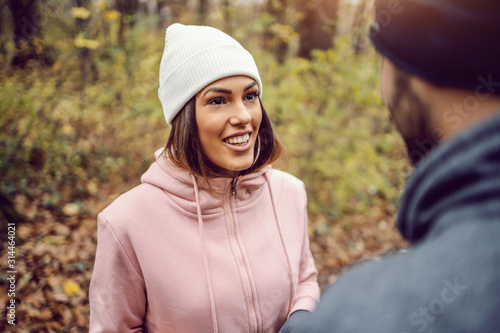 Obraz Pretty smiling young woman in sportswear, with beanie on head standing in nature,taking a break and talking to her friend. Fitness in nature on cold weather concept. - fototapety do salonu