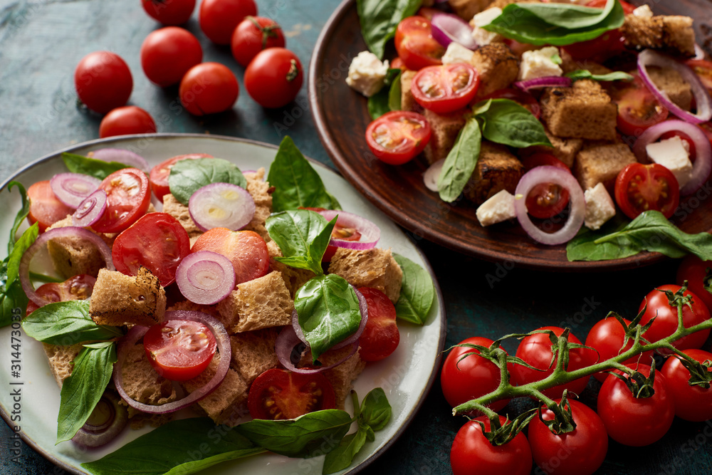 Fototapeta fresh Italian vegetable salad panzanella served on plates on table with tomatoes