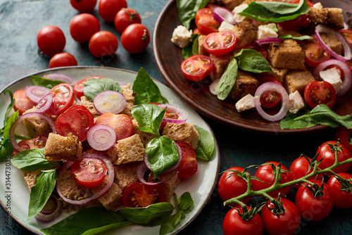 Fototapeta fresh Italian vegetable salad panzanella served on plates on table with tomatoes obraz