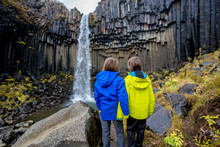 Happy Child, Posing In Front Of Beautiful Waterfall Svartifoss In Skaftafell National Park