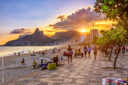 Photo Sunset view of Ipanema beach with mosaic of sidewalk, Leblon beach and the Mountain Dois Irmao in Rio de Janeiro