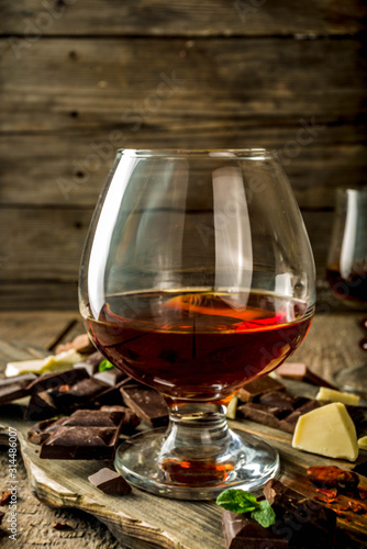 Strong alcohol drink. Glass of brandy, whiskey or cognac on the wooden table