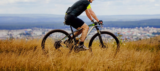 male cyclist riding trail of dry grass in mountain bike