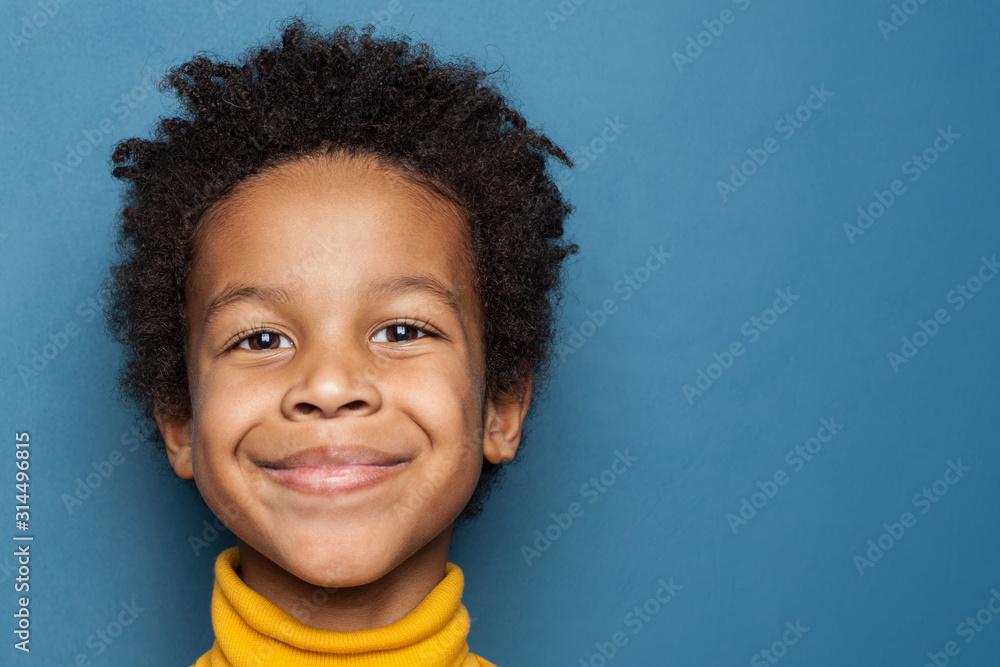 Fototapeta Smiling kid boy portrait. Little african american child boy on blue background