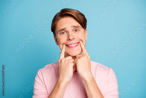 Fotografie, Obraz Portrait of negative unhappy guy making fake smile on his face with fingers wear