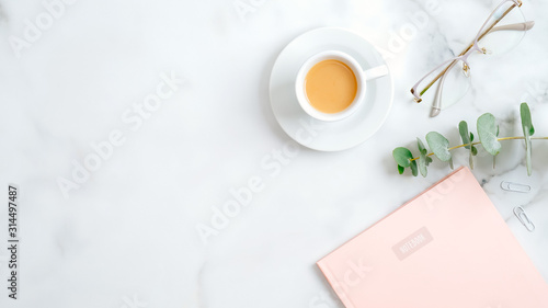 Cozy home office desk table with pink paper notebook, glasses, eucalyptus leaf, coffee cup on marble background Wallpaper Mural