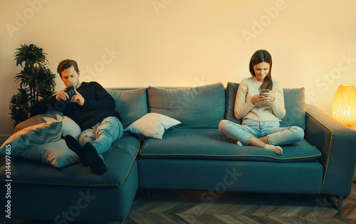 Smartphone addicted couple use phones sit on sofa at home, overuse social media, internet addiction concept Canvas Print