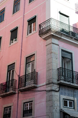 Traditional Portuguese apartments, painted pink, taken on a sunny summer day in Lisbon.