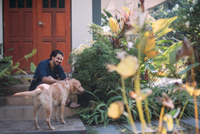 A Man With Dogs Sits On The Porch Of A House In A Tropical Garden.
