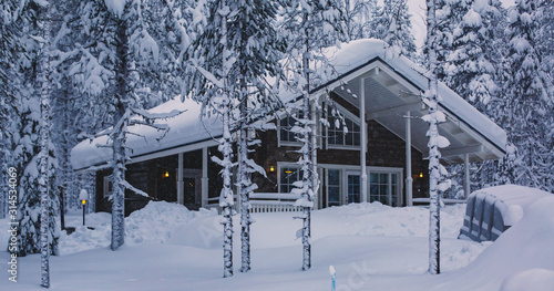Valokuvatapetti A cozy wooden cabin cottage chalet house covered in snow near ski resort in wint