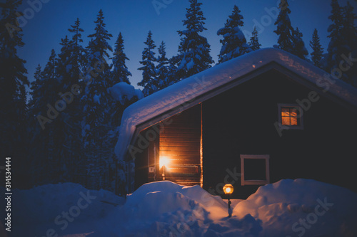 Obraz na plátne A cozy wooden cabin cottage chalet house covered in snow near ski resort in wint