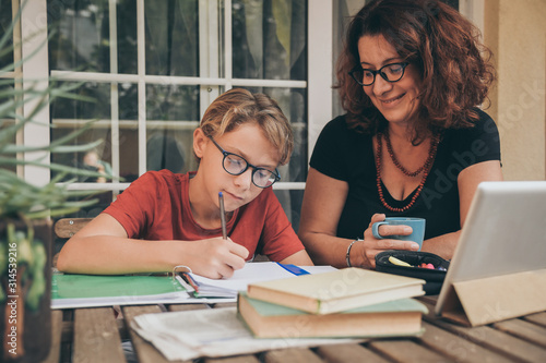 Young student doing homework at home with school books newspaper, digital pad helped by his mother Canvas Print