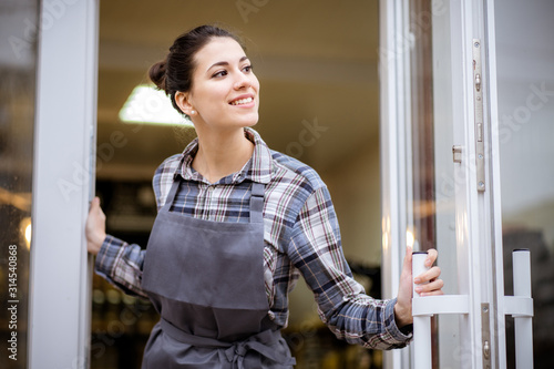 Fényképezés Beautiful asian woman store owner with standing in the doorway of her coffee shop looking at camera and smiling