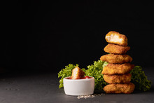 Cooked Chicken Nuggets In Breadcrumbs With Lettuce And A Bowl Of Ketchup On A Dark Background With Place For Text
