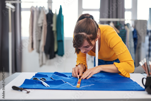 Fotografie, Obraz Creative caucasian fashion designer standing in her studio and drawing scheme on blue linen for a beautiful night dress
