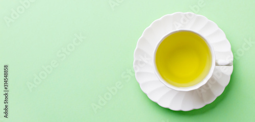 Green tea in a white cup on pastel green background Fototapeta