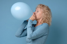 Beautiful Senior Blonde Woman Preparing For Party Blowing Up Blue Balloon