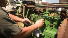 Close Up Of Agricultural Mechanic Working On An Antique Farm Tractor