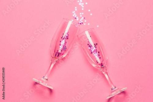 Two champagne glasses with splash of pink stars shaped confetti over pink background. Top view. Valentine's Day concept