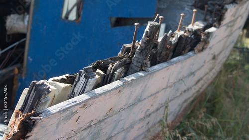 Close up of broken hull of abandoned boat; exposed beams and nails - Alaska #314557615