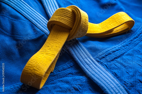 Yellow judo belt tied in a knot layng on blue judogi Tablou Canvas
