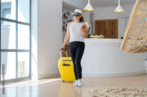 Fotografie, Tablou Woman guest tourist with suitcase in hotel lobby interior.