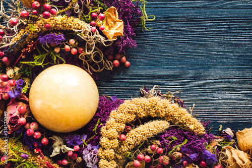 Yellow Aventurine Sphere with Dried Flowers and Moss on Blue Background