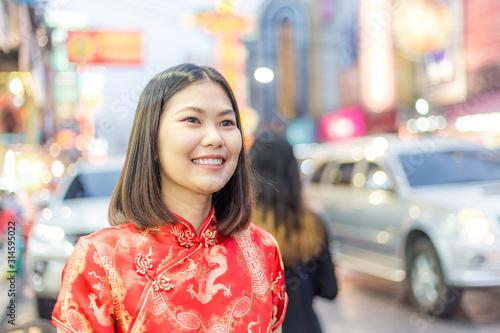 Beautiful smiling asian women with chinese costume red dress travel in China town Yaowarat street