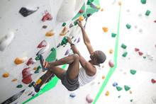 Sportive Man Climbing A Wall In A Climbing Centre