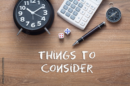 Things to consider written on wooden table with clock,dice,calculator pen and co Fototapet