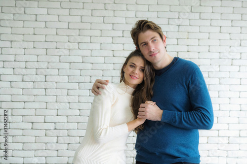 European couples, caucasian man wearing blue sweater and woman wearing white sweater, are standing happily hugging each other in the room Canvas Print
