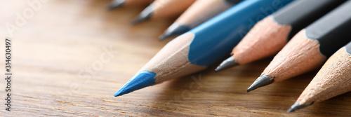 Photo Blue pencil spy between black pencils