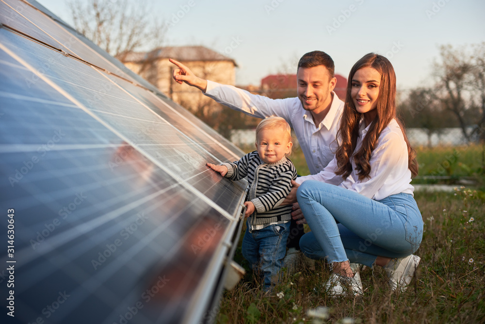Fototapeta A young family of three is crouching near a photovoltaic solar panel, smiling and looking at the camera, concept of bright future