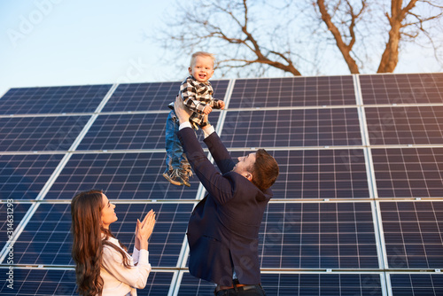 Fototapeta Low angle view of a happy family spending fun time at solar plant, father holding his son above their heads, mother clapping hands obraz