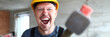 canvas print picture - Portrait of screaming male holding big sturdy construction tool. Scary builder laughing at camera with joy and madness. Strange guy wearing yellow hardhat and bricklayer outfit. Building concept