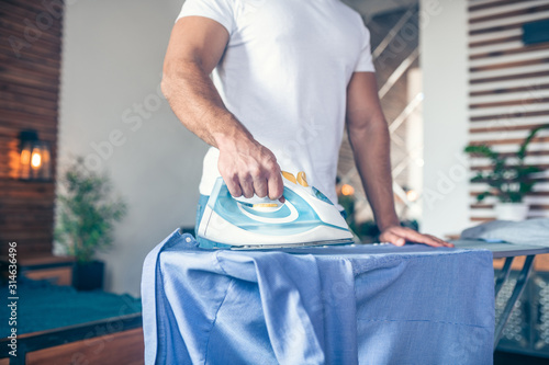 Dark-haired young man in white tshirt ironing his shirt Fototapet
