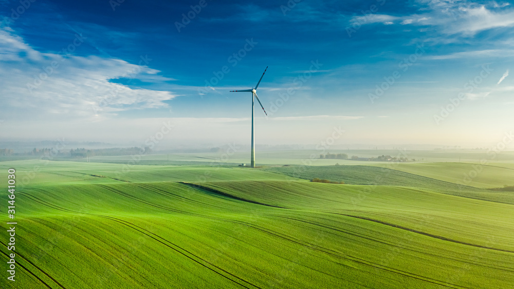 Fototapeta Wind turbine on green field at sunrise, view from above