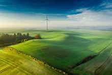 Wind Turbine On Foggy Green Field At Sunrise