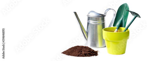 watering can, flowerpot and gardening tools behind heap of dirt on white background